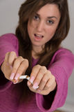 Out of focus portrait of woman breaking a cigarette in two Royalty Free Stock Image
