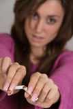 Out of focus portrait of woman breaking a cigarette in two Stock Photography