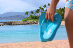 Out of focus of woman holding a pair of flip flops Stock Photos