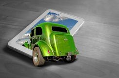 Out of frame classic vintage car driving into computer screen. Concept photo of a vintage car driving into a tablet computer screen blank space ideal for own royalty free stock images