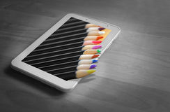 Out of frame tablet colouring pencils. Photo of out of frame colouring pencils protruding from tablet device Royalty Free Stock Image