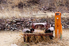 Out of gas. An old rusty car with weeds growing up through the bumper is parked beside a gas pump. Words on the car say Don't touch! and Keep Off royalty free stock photos