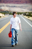 Out of gas. Male teenager with gas can walking on a mountain road in late sun stock image