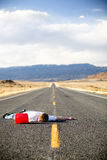 Out of gas. Teen male laying dead in the middle of a remote rural highway still clinging to red gas can royalty free stock photo