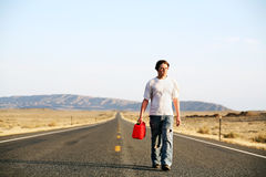 Out of gas. Teenager male walking down rural highway with empty red gas can royalty free stock photo