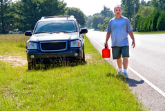 Out of Gas. A man who has run out of gas with a gasoline can stock image
