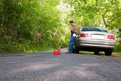 Out Of Gas. Upset man stranded on a country road, with a gas can at his feet Stock Images