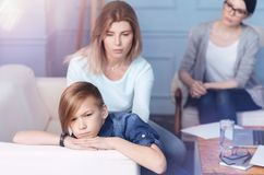Out of humor boy ignoring mom during psychological seance. Please look at me. Grumpy male youngster getting irritated while attending a child psychologist with Royalty Free Stock Photos