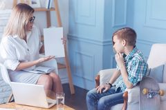 Out of humor problem youngster passing psychological test. What do you see. Serious boy resting his chin on his hand and focusing his attention on a sheet of Royalty Free Stock Photos