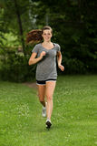 Out for a jog. Attractive woman trail running outside Stock Photography