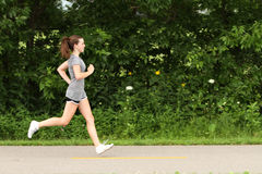 Out for a jog. Attractive woman trail running outside Royalty Free Stock Image