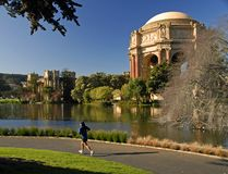 Out for a jog. Girl jogging past the Palace of Fine Arts in San Francisco, CA Royalty Free Stock Image