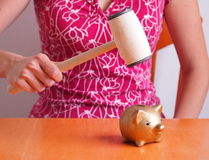 Out of money. A woman in a pink shirt who wants to break the golden piggy bank with a meat mallet royalty free stock photo