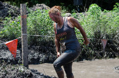 Out of the muddy water. A young woman climbs out of the muddy water onto firmer ground, and towards the next obstacle in this dirty race called a mudathlon Stock Photography