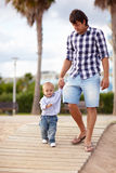 Out and about with my dad. Contemporary father helping his son walk down to the beach Stock Image