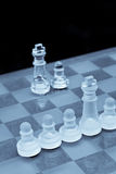 Out Numbered. Unfair Competition concept with use of glass chess pieces in selenium lighting Royalty Free Stock Images