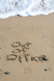 Out of office text written in sand on a beach Royalty Free Stock Photography