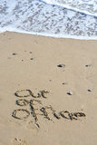 Out of office text written in sand on a beach Royalty Free Stock Images