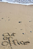 Out of office text written in sand on a beach Stock Images
