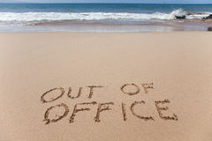 Out of office written in the sand on a beach Stock Image