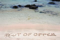 OUT OF OFFICE written on sand on a beautiful beach, blue waves in background Stock Photos