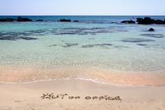 OUT OF OFFICE written on sand on a beautiful beach, blue waves in background Stock Photography