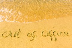 Out of office written on sand. Sandy beach with Out of office sign scribbled on beach sand. leisure time concept royalty free stock images