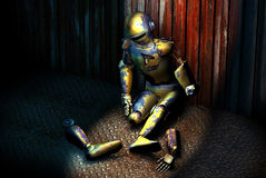 Out of order. Broken robot who rests on a metallic floor and is leaned on a metallic wall Stock Photo