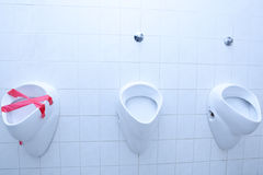 Out of order concept - out of order urinal. Out of order concept - man restroom with three urinals/pissoirs out of which one is out of order (color toned image Royalty Free Stock Images