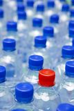 Out of ordinary. Bottled drinking water with blue cups and one red cup Stock Photography