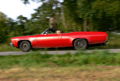 Out for a Ride. Three women enjoying the sun in their shabby red convertible while driving down a small country road Stock Images