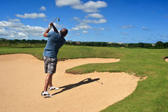 Out of the sand trap. Golfer successfully hitting golf ball out of a sand trap Royalty Free Stock Images