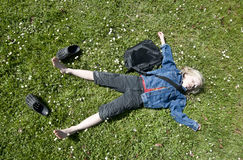 Out of school. Young blond boy taking a breather on the lawn after school Royalty Free Stock Images