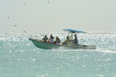 Out on the sea. People on a boat in the Caribbean Sea in Aruba Royalty Free Stock Photos