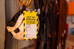 Out of service tag attached on faulty defect safety fall protection abseiling helmet royalty free stock photos