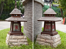 In and out signs on Asian wooden lanterns in a shape of pagoda. Directional lamps at entrance and exit - inside and outside Royalty Free Stock Images