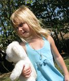 Out And About With Teddy. Pretty little girl playing outside with her teddy bear in tow Stock Photo