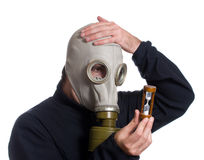 Out of Time. A man wearing a gas mask is looking at an hour glass realizing he is out of time, isolated against a white background Stock Images