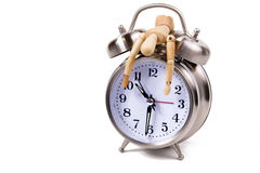 Out of Time. Wooden mannequin draped over an alarm clock.  Conceptual image for Out of TIme.  Isolated on white Stock Images