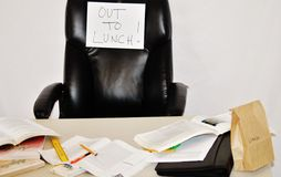 Out to lunch. Forgotten brown bag lunch on desk Stock Photos
