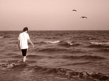 Out to Sea. Young man walking out to sea stock image