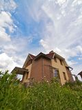 Out-of-town house on a grass-plot. Wide angle shot of a cottage in garden royalty free stock images