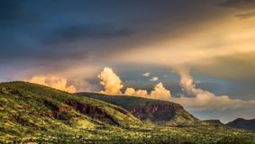 Outback Australia. Sunlight bursts though the storm clouds and illuminates the Hamersley Ranges.  Karijini National Park, Outback Australia Stock Photos