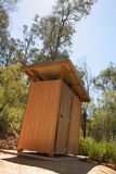 Outback dunny; tall view, angled. A fair dinkum outback dunny in an Australian forest reserve. A dunny is a toilet, for those who don't know Royalty Free Stock Image