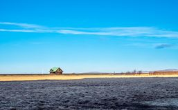 Outback field in Iceland. Outback field with colorful farm and small house in Iceland, under blue sky in winter season Royalty Free Stock Images