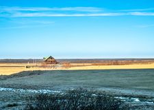 Outback field in Iceland. Outback field with colorful farm and small house in Iceland, under blue sky in winter season Royalty Free Stock Photography