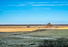 Outback field in Iceland. Outback field with colorful farm and small house in Iceland, under blue sky in winter season Royalty Free Stock Photo