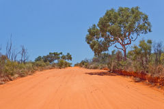 Outback Road. Red sandy outback road in the Australian desert against a brilliant clear blue sky Stock Photo