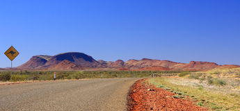 Outback road. Rocks , australien sign and blue sky royalty free stock photography