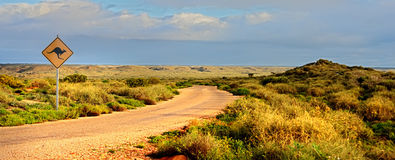Outback road. Rocks , australien sign and blue sky stock images